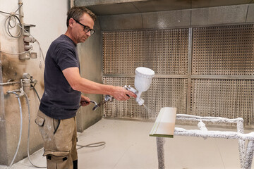 Side view of serious middle aged carpenter using spray gun for painting wood detail with white foamy flame retardant while working in light modern workroom