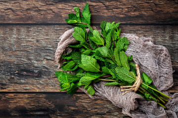 Top view of bunch of fresh green aromatic mint twigs arranged on rustic wooden table