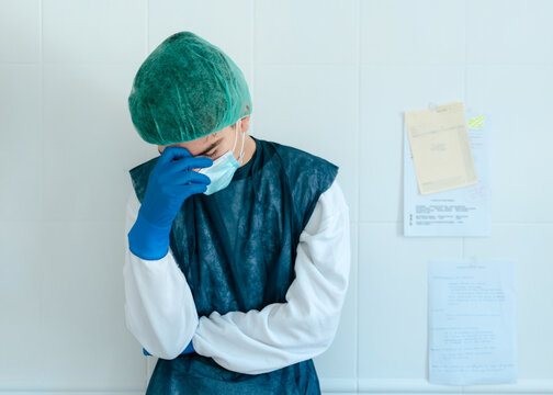 Exhausted young medical worker in protective costume and mask with gloves standing near wall in hospital corridor while working hard during coronavirus pandemic