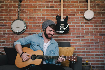Cheerful bearded guitarist in sock cap and denim jacket playing acoustic guitar while sitting on couch with decorative pillow near brick wall with different musical instruments at home