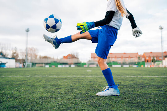 Low angle side view of unrecognizable teenage girl in white and blue uniform and goalkeeper gloves kicking ball while training alone in football arena at stadium in daytime