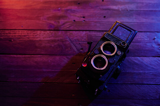 From above top view of retro photo camera placed on wooden table in modern dark studio