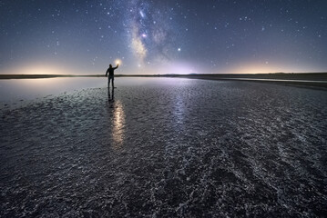Back view of anonymous man standing and holding torch on empty road among calm water and reaching out to star under colorful nigh sky with milky way on background