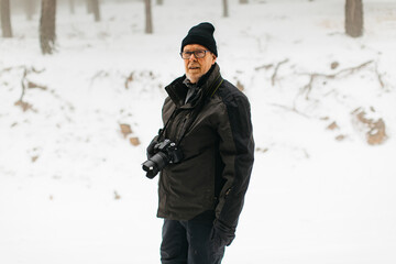 Side view of a senior male with a camera in the snow