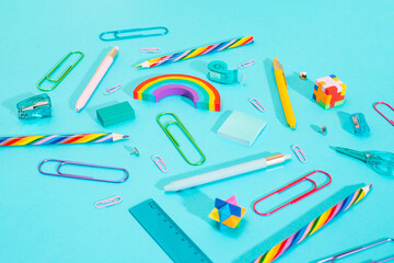 Close-up view of a bunch of colorful school supplies over blue background