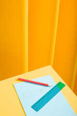 Red pencil and blue ruler with papers and draws over a yellow table