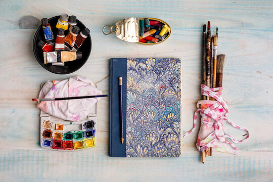 Top view of creative sketchbook and paintbrushes arranged on table with watercolor and pastel colors