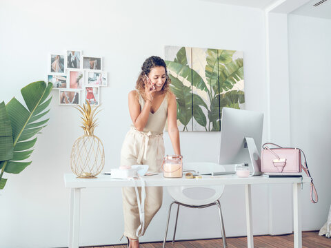 Pretty woman in elegant outfit smiling and having phone conversation while standing near desk in stylish office