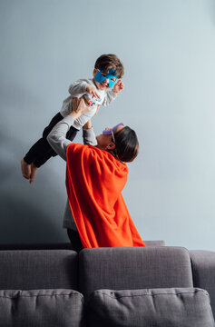 Side view of playful woman in superhero mask and cloak tossing little boy while spending time together at home and having fun