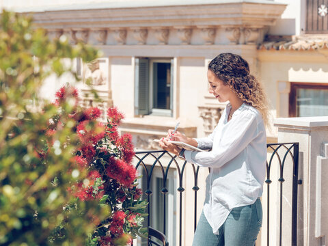 Side view of attractive young woman smiling and writing in notebook while leaning on railing of beautiful terrace