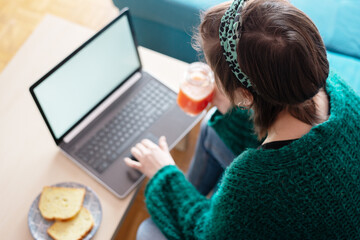 Top view of a woman having breakfast while working at home on her laptop