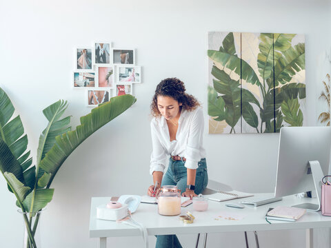 Charming young female in stylish elegant outfit standing near office desk and writing