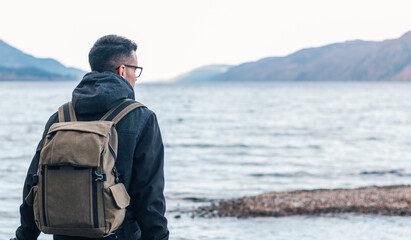 Back view of male hiker in warm jacket with backpack sitting on wooden bench near sea and enjoying marine scenery with rocky coast during travel in Scotland