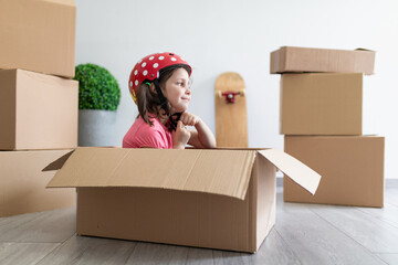 Side view of happy little girl smiling and fastening helmet while sitting in cardboard box and playing during relocation