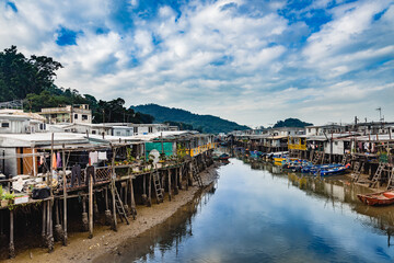 Deurstickers Stad aan het water Perspective view of peaceful city river with small houses and wooden piers on both sides under bright cloudy sky in Hong Kong