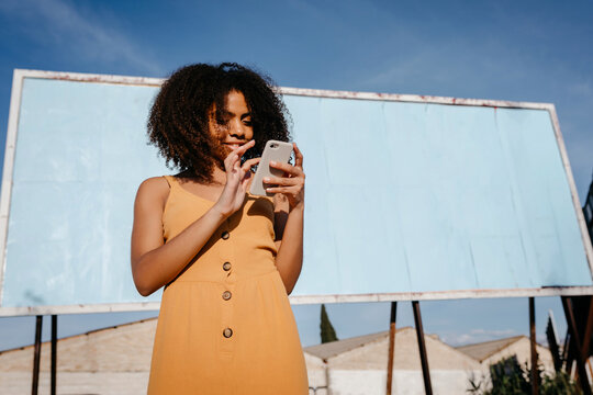 African American girl interacting with cellphone standing alone against blank billboard in city