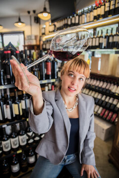 Charming stylish woman in gray jacket exploring color of red wine in glass having time in wine house.
