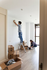 Young man standing on ladder hammering nail and woman picking instruments from bag in apartment with carton boxes