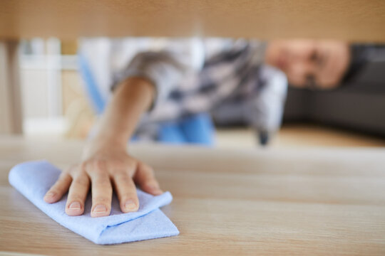 Close-up of young woman wiping the dust with rag under the bed in the room