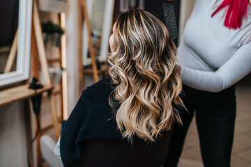 Beautiful hairstyle of young woman after dyeing hair and making highlights in hair salon.