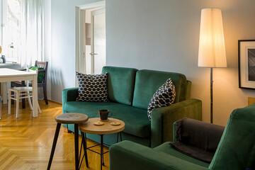 Fototapeta wnętrz - ciemnozielona sofa i fotel, obok lampa, stolik i taboret, na podłodze parkiet drewniany. obraz