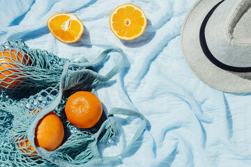 Picnic flatlay of oranges in an eco string bag and hat on blue blanket