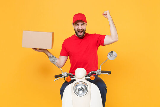 Delivery man in red cap tshirt uniform driving moped motorbike scooter hold cardboard box isolated on yellow background studio Guy employee working courier Service quarantine pandemic covid-19 concept
