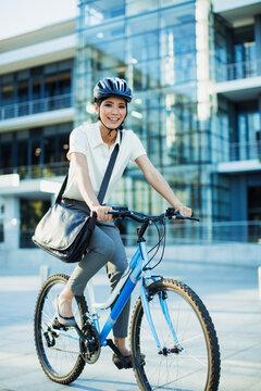 Smiling woman bike riding on urban sidewalk