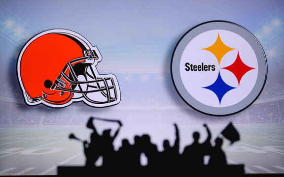 Cleveland Browns vs. Pittsburgh Steelers. Fans support on NFL Game. Silhouette of supporters, big screen with two rivals in background.
