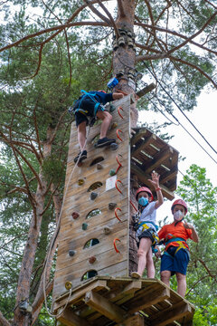 group of children practicing multiadventure climbing wall and zip lines with mask