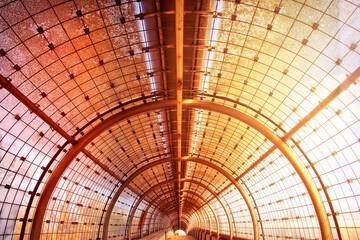 Glastunnel, lichtdurchflutet in orangem Sonnenschein