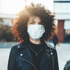 Young curly haired woman wearing a medical mask outside posing at camera in a sunny day