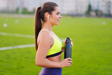 A beautiful young sportswoman is engaged in fitness outdworth. Drinks water from a bottle.