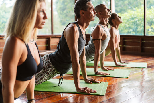 Group Of People Practicing Yoga In Class.