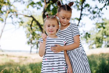 Little girl crying outdoors. The older sister takes care of her younger sister. Girlfriends