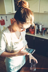 The girl with the phone in the kitchen