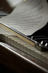 Selective focus shot of a violin bow and sheet music on piano keys