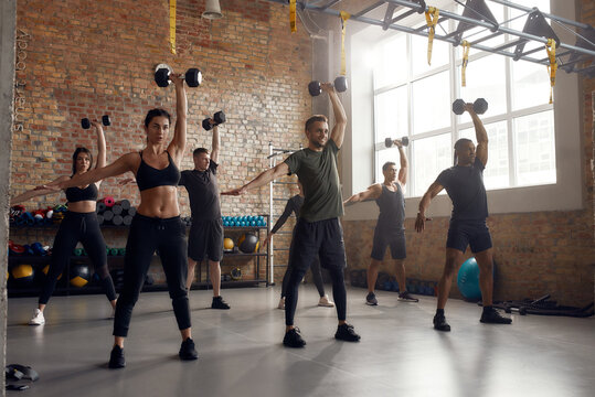 We can do hard things. Full length shot of group of sportive people lifting dumbbell while having workout at industrial gym. Group training, teamwork concept