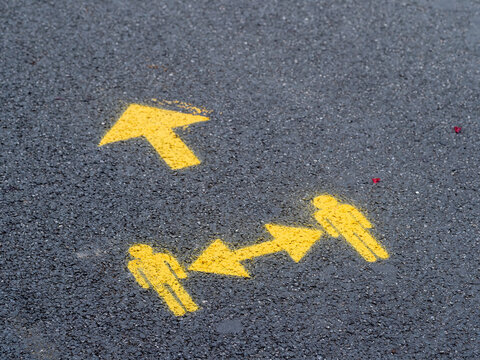 Yellow socially distanced and one way directional sign for pedestrians in street. UK Covid precaution.