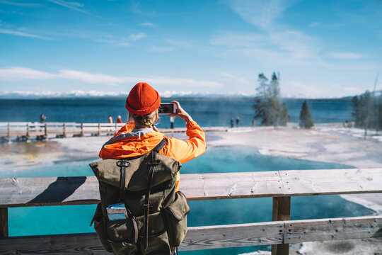 Back view of female tourist with backpack using smartphone for taking picture of hot springs, hipster wanderlust making image on smartphone camera of touristic place in USA with geyser in Yellowstone