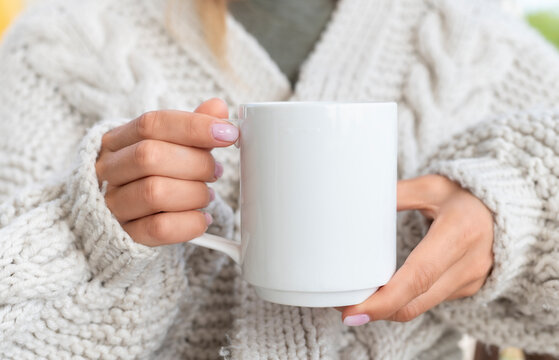 White ceramic mug mockup. Woman in Sweater Holding a Warm Cup of Coffee. Copy space for your print