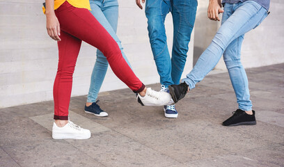 Young people greeting to avoid the spread of coronavirus - Friends meet, instead of greeting with hug or handshake, they touch their feet together - Social distancing concept - Focus on closeup shoes