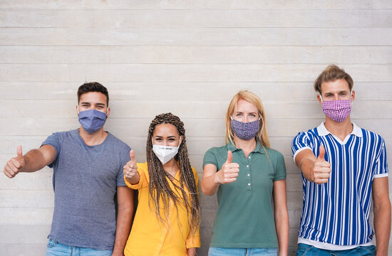 Young people with thumbs up wearing face protective masks for coronavirus prevention - Covid 19 lifestyle and millennial generation, social distance concept - Main focus on center faces