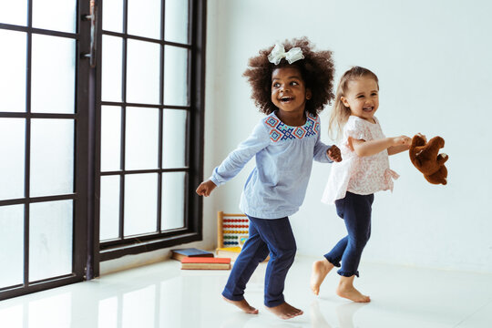 Candid portrait of two energetic playful young diverse friends children playing indoors. African American and Caucasian girls together
