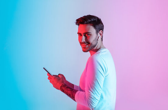 Devices for young people. Smiling guy with wireless headphones and smartphone in neon light