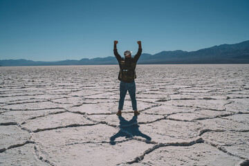 Back view of male wanderlust with touristic backpack raising arms completed marathon in Badwater...