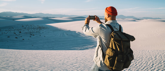 Man with touristic backpack using app on smartphone for making pictures in desert traveling on vacations, back view of hipster guy wanderlust taking photo of White sands national park on cellphone