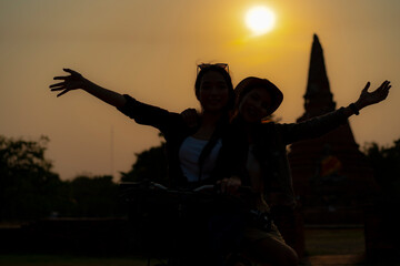 Silhouette of two female with bicycle at Ayutthaya Historical Park, Thailand.