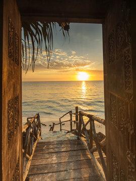 Beautiful dor way to white beach with sunrise in background. Zanzibar