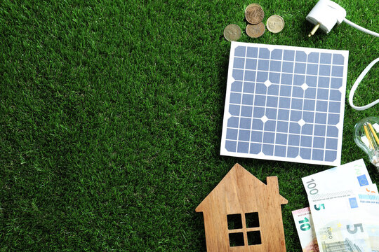 Flat lay composition with solar panel, house model and money on green grass. Space for text